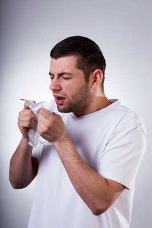 estornudo: Hombre joven enfermo en camiseta blanca estornudar en limpiar debido a la gripe Foto de archivo