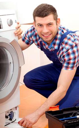 Professional handyman in blue uniform repairing a washing machine in bathroom photo