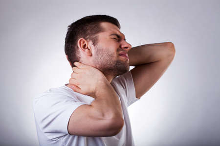 'head and shoulders': Young exhausted man with strong neck ache isolated on white background Stock Photo