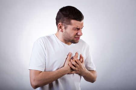 dolor en el pecho: Hombre joven en camiseta blanca con un fuerte ataque al coraz�n Foto de archivo