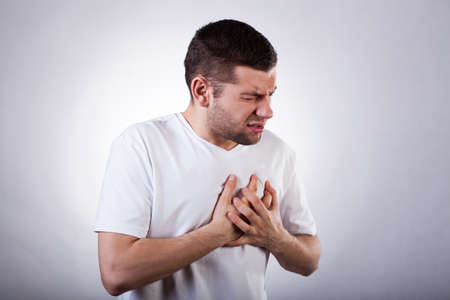 pain: Young man in white t-shirt with strong heart attack