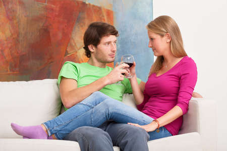 Young marriage relaxing at home and drinking wine photo