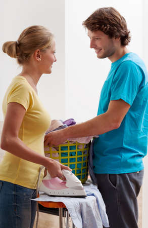 A couple in love ironing clothes from a basket photo