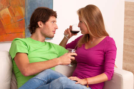 Young beautiful couple drinking wine spending time at home photo