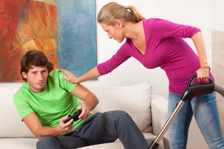 vacuum cleaning: Woman who cleaning house is angry for her lazy partner Stock Photo