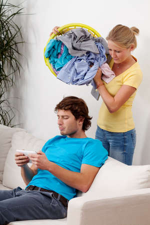 A woman about to throw laundry on her lazy husbands head photo