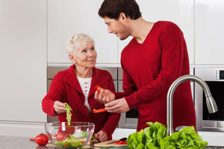 bowl sink: Elderly lady with her son making salad together