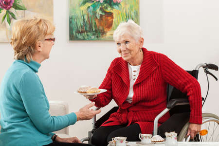 Disabled old lady offering a cupcakes to her friend photo