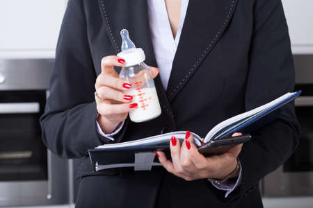 businessowman: An elegant businesswoman working while holding her childs milk bottle