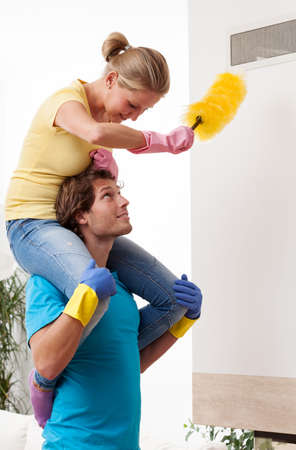 dusting: A woman dusting at altitudes while on her husbands shoulders Stock Photo