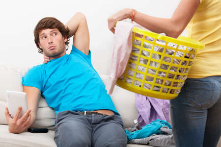 Lazy partner using tablet when woman cleaning his clothes photo