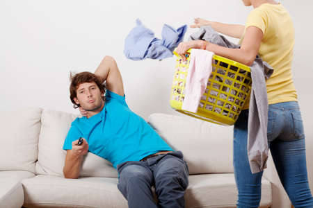 A woman with a laundry basket and a man watching tv photo
