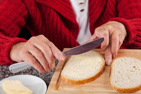 朝食のパンにバターを広がっている高齢者の女性