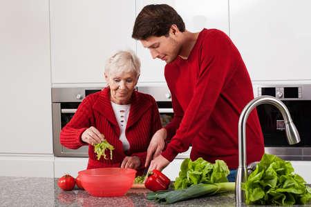 grandson: Adult grandson helping his grandma in kitchen
