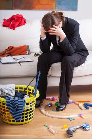 habitacion desordenada: Empresaria infeliz que se sienta en el medio de un l�o de sus hijos hicieron Foto de archivo