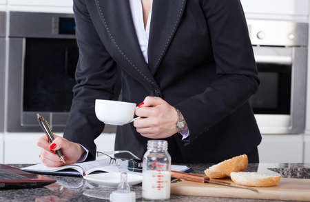 W 사업가 커피를 마시는, 작업 및 그녀의 아이들을위한 식사를 만들기