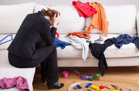messy clothes: An unhappy woman sitting on a sofa in a messy living room Stock Photo