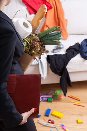 perfectionist: A businesswoman standing in messy home with shopping bags Stock Photo