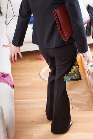 A woman iritated by mess after having come home from work wand shopping photo