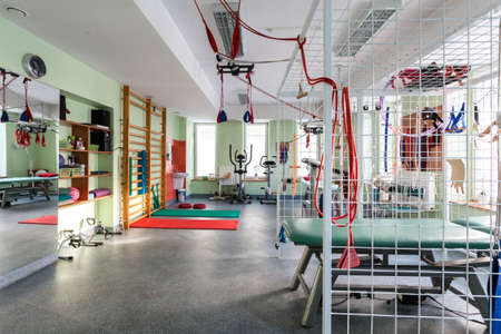 rehab: Colorful modern gym equipped with exercise machines Stock Photo
