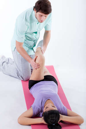 Doctor examining a patient leg at physiotherapy center Stock Photo