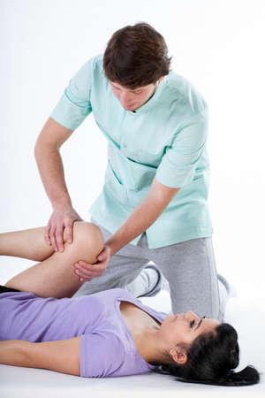 masaje deportivo: Fisioterapeuta haciendo una rehabilitación de la rodilla al paciente en el centro médico Foto de archivo
