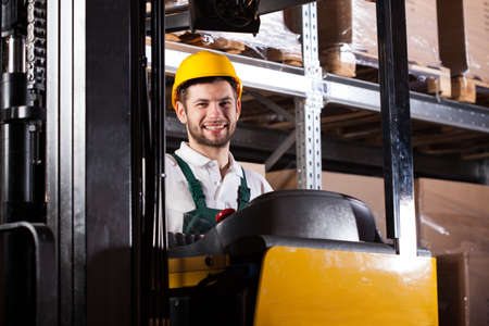 warehouse worker: Warehouse worker in yellow hardhat working on forklift and smiling Stock Photo