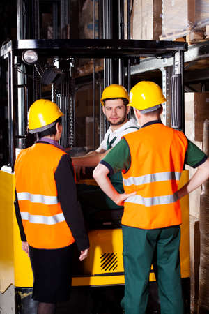 Pair of managers talking with young forklift worker at warehouse photo