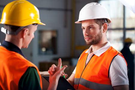 supervisores: Dos trabajadores del almacén discutir sobre el nuevo proyecto