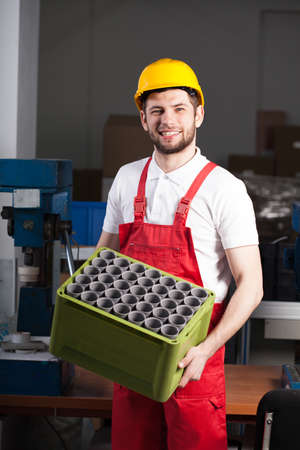 Factory worker holding box with equipment during work photo