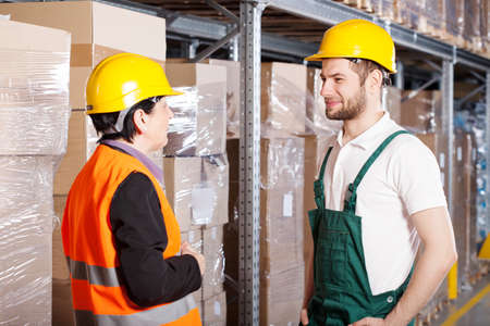 Manager of factory talking with young warehouse worker photo