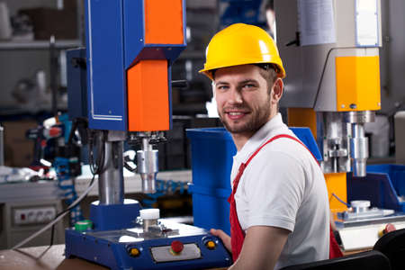 Young handsome factory worker in yellow helmet during work photo
