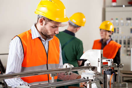 production process: Factory worker in yellow helmet working on the machine  Stock Photo