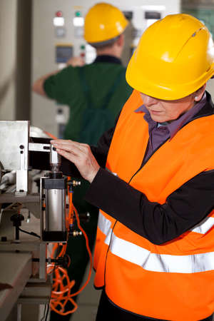 assembly line: Engineer woman working on professional factory machine