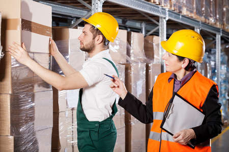 Manager ordering to worker how to pack cartons in warehouse photo