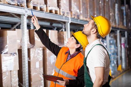 pallet: Ingeniero Almacén ordenando a los trabajadores cómo trabajar Foto de archivo