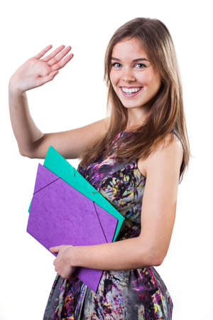 Young student in colorful dress waving hand in farewell photo