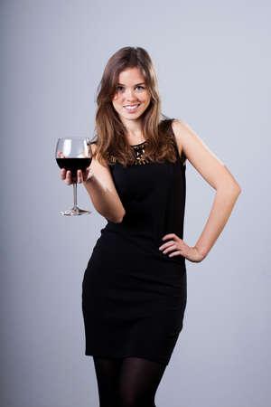 vestido de noche: Mujer de la elegancia vestida en traje de noche la celebración de vidrio con vino
