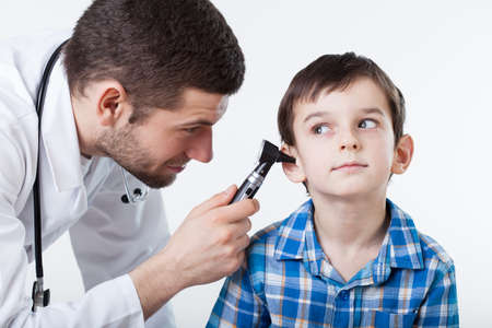 Physician performing ear examination during a visit Stok Fotoğraf