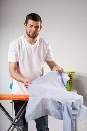 Husband helping at home and ironing shirts photo