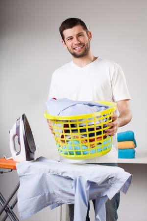 Happy handsome husband doing laundry and ironing photo