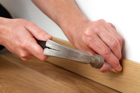 hammering: Mans hands hammering a nile into a skirting board Stock Photo
