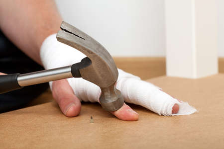 pinched: A hurt bandaged hand pinched by a hammer Stock Photo