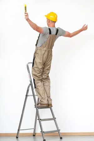 hombre cayendo: Trabajador con el casco amarillo que cae de escalera de aluminio