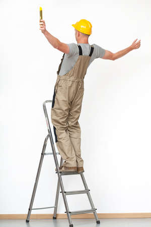 Worker with yellow helmet falling from aluminium ladder