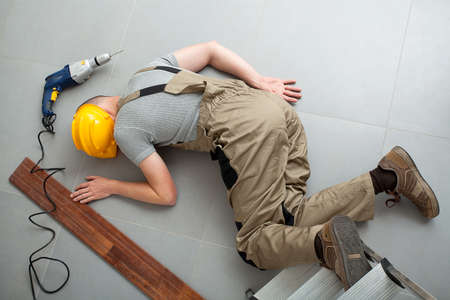 accident at work: A worker injured during a bones braking fall