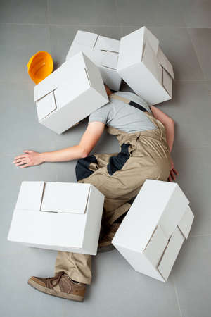 Unconscious handyman lying crushed by heavy cartons  photo