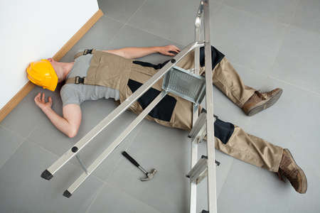 pinched: A worker pinched by a ladder which has fallen on him