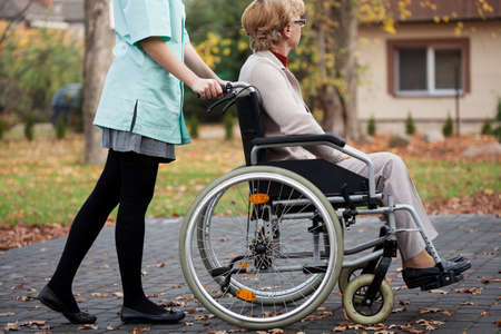 2 people: Caregiver on  a relaxing walk with elder woman on wheelchair