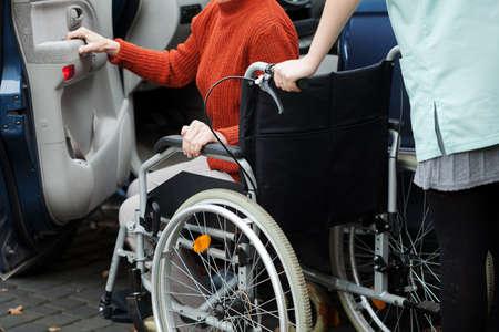 Verzorger helpen dame uitgeschakeld in de auto